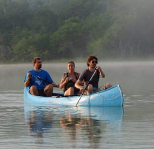 Paddling a Canoe through early morning mist rising from lake